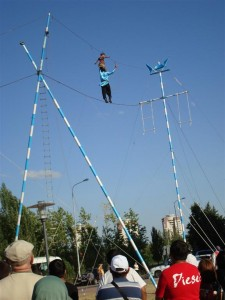 Oldest (Apparently, In Central Asia) Tightrope Walker. Small Girl Balancing On His Shoulders.