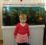 Anna In Baba's Homemade Dress In Front Of Fish
